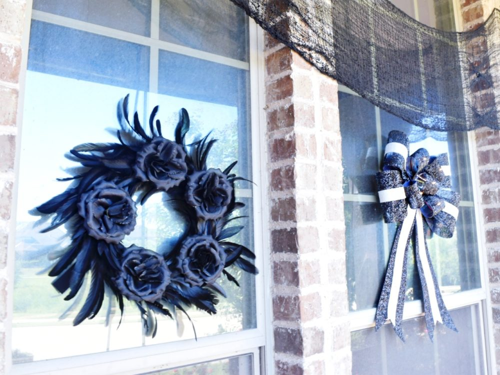 Frightful front porch modern chic halloween decorating ideas modern Halloween decor black feather wreath with black roses black and white striped bow how to decorate for Halloween