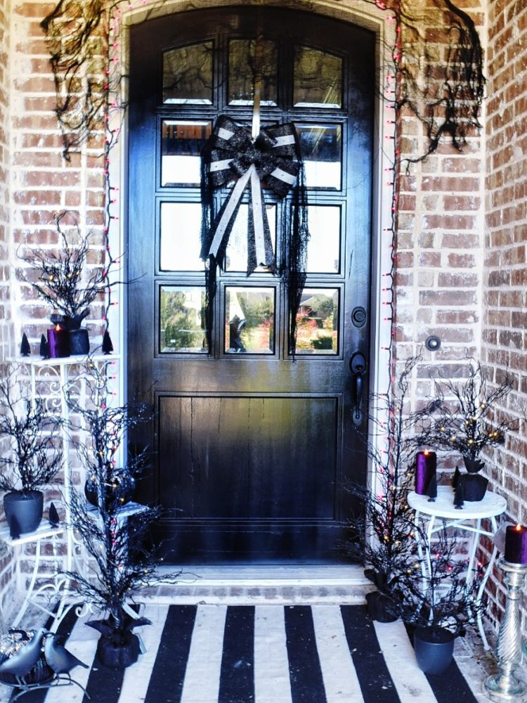 Frightful front porch modern chic halloween decorating ideas black front door with black and white LED pre lit bow modern Halloween decor