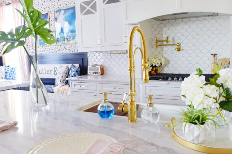 Modern Coastal Glam Kitchen Makeover Coastal Kitchen Design Ideas white farmhouse sink marble countertops marble kitchen island brass faucet brass pot filler coastal backsplash white backsplash