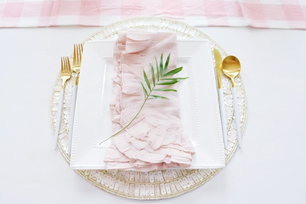 gorgeous spring table setting ideas using tropical palm leaves, ruffled table napkins, pink gingham tablecloth