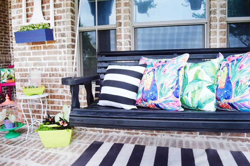black front porch swing with colorful pillows