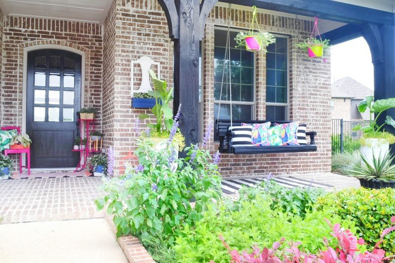 front porch with swing and colorful plants and decor