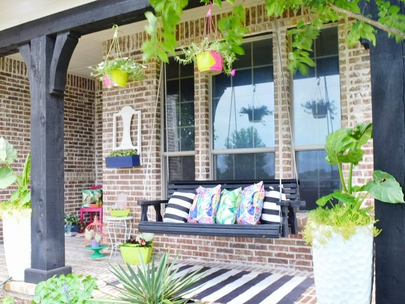 front porch swing with tropical pillows and decor
