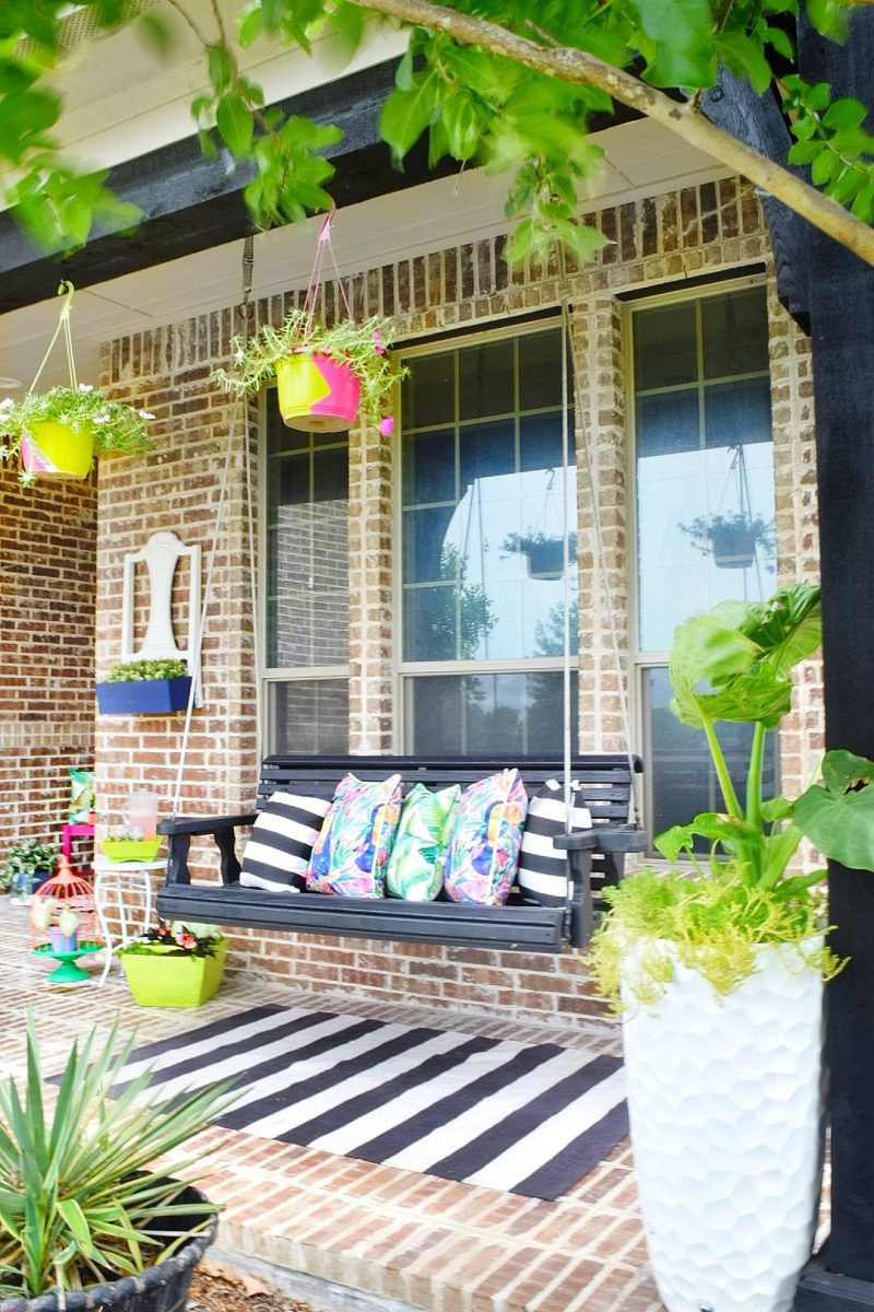 front porch swing with flower pots and hanging planters