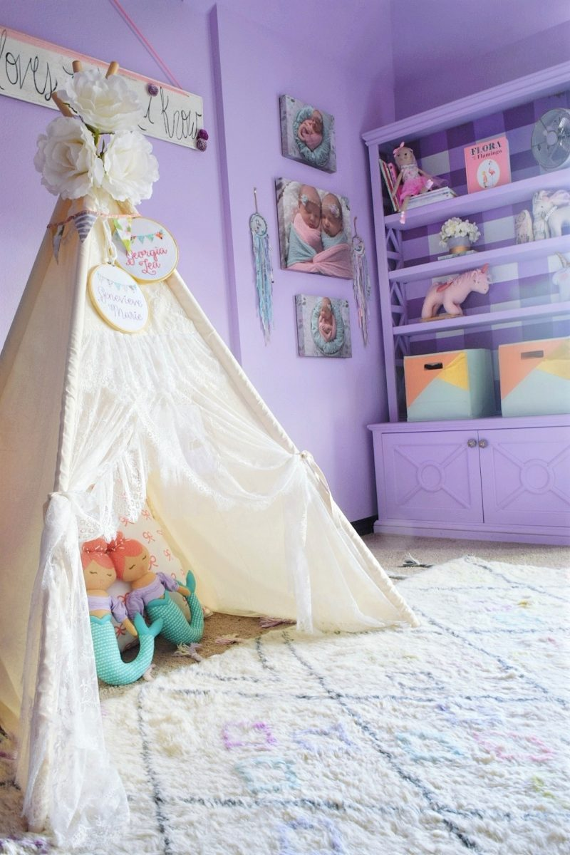 little girls bedroom with teepee with light purple bookcase and buffalo check print