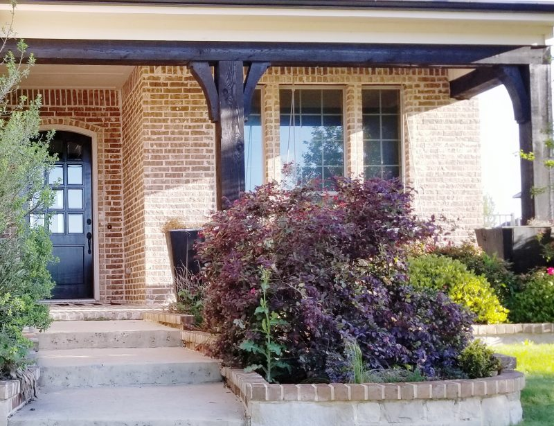 front porch and gardens of brick home