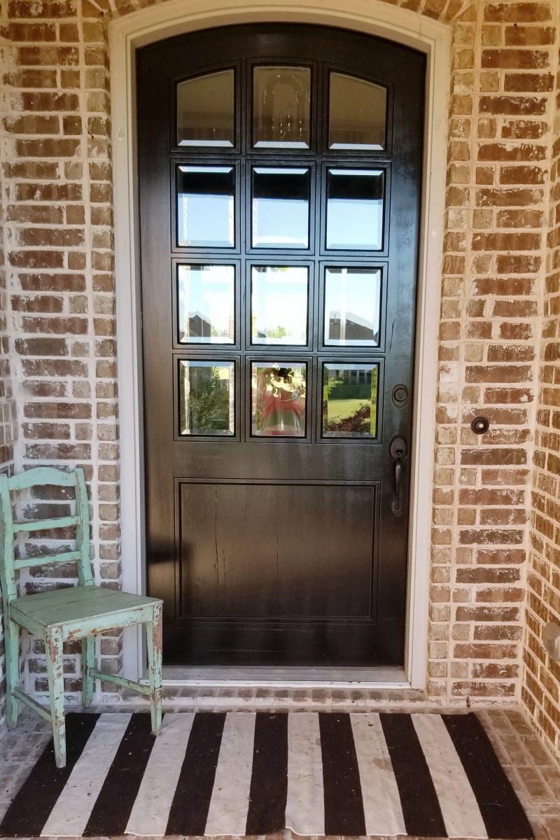 wooden front door of brick house with chippy green chair