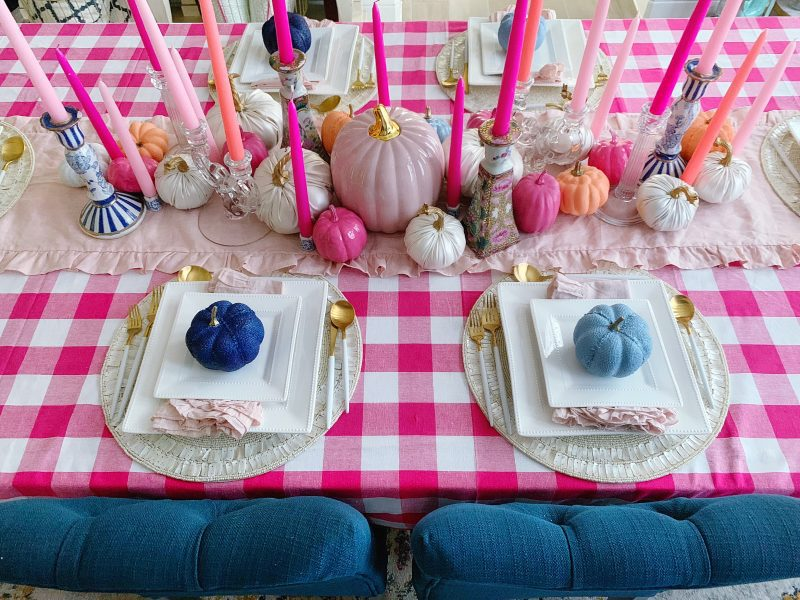 fall tablescape with pink pumpkins and blue pumpkins, pink gingham tablecloth and pink taper candle centerpiece