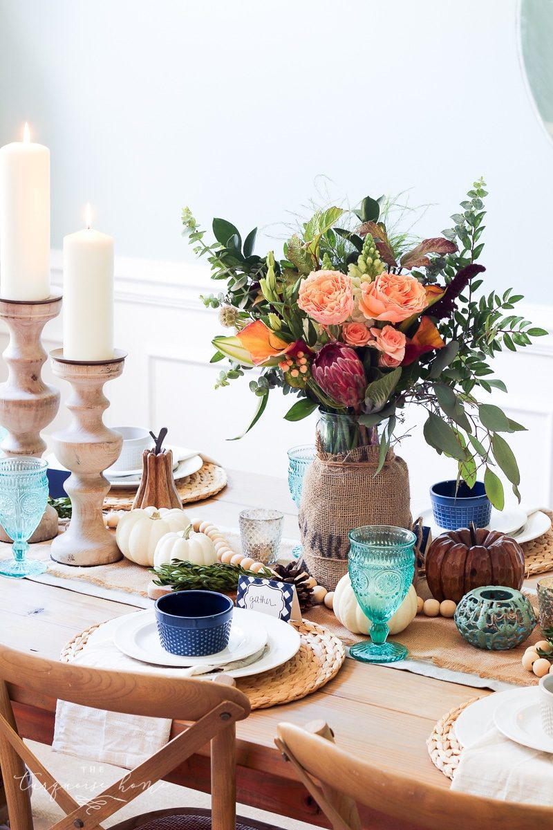 farmgirl flowers fall centerpiece with pillar candles and turquoise blue drinking glasses