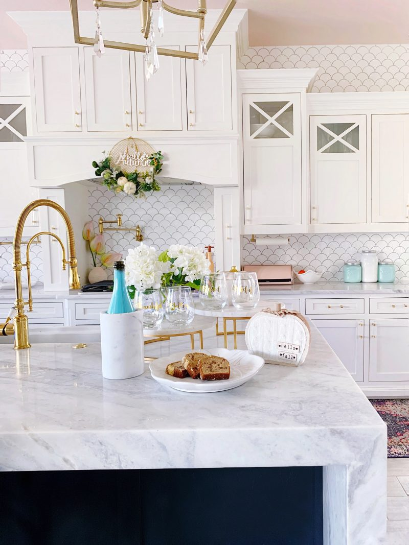 white kitchen with white cabinets and countertops with fall tabletop decor accents
