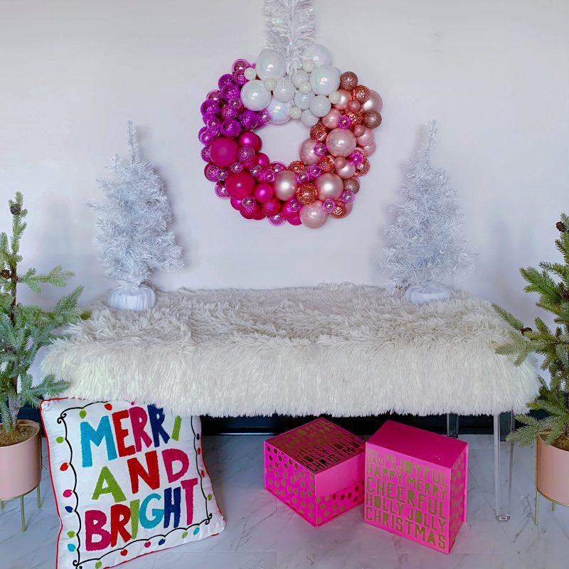 pink christmas wreath with white christmas trees pink christmas gift boxes and christmas pillow
