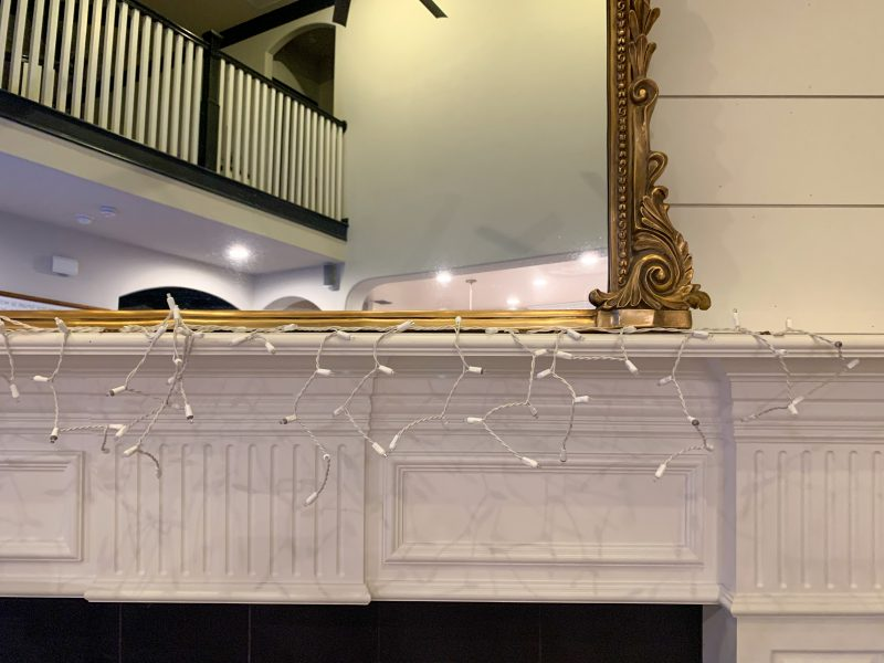fireplace mantel with shiplap wall and leaning mirror