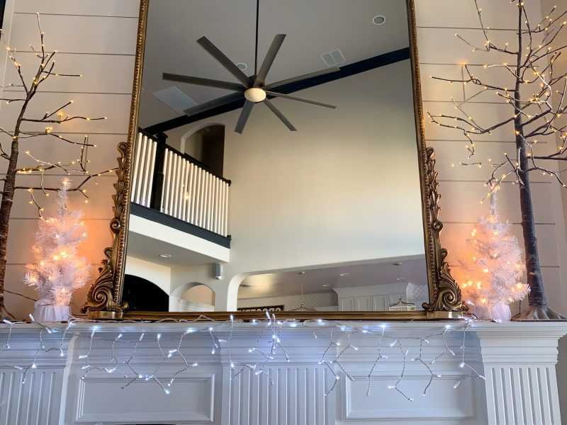 white mantel shiplap wall with christmas trees and mirror