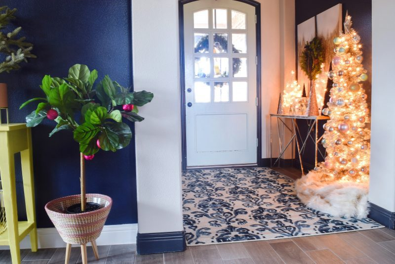 front door entryway with blue and white rug and dark painted accent walls