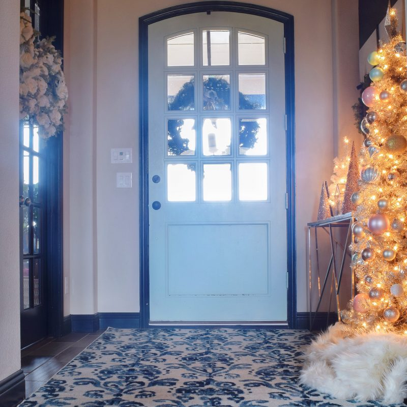 front door entryway Christmas decor with Christas tree and rug