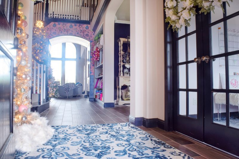 entryway with pink wallpaper and blue and white rug
