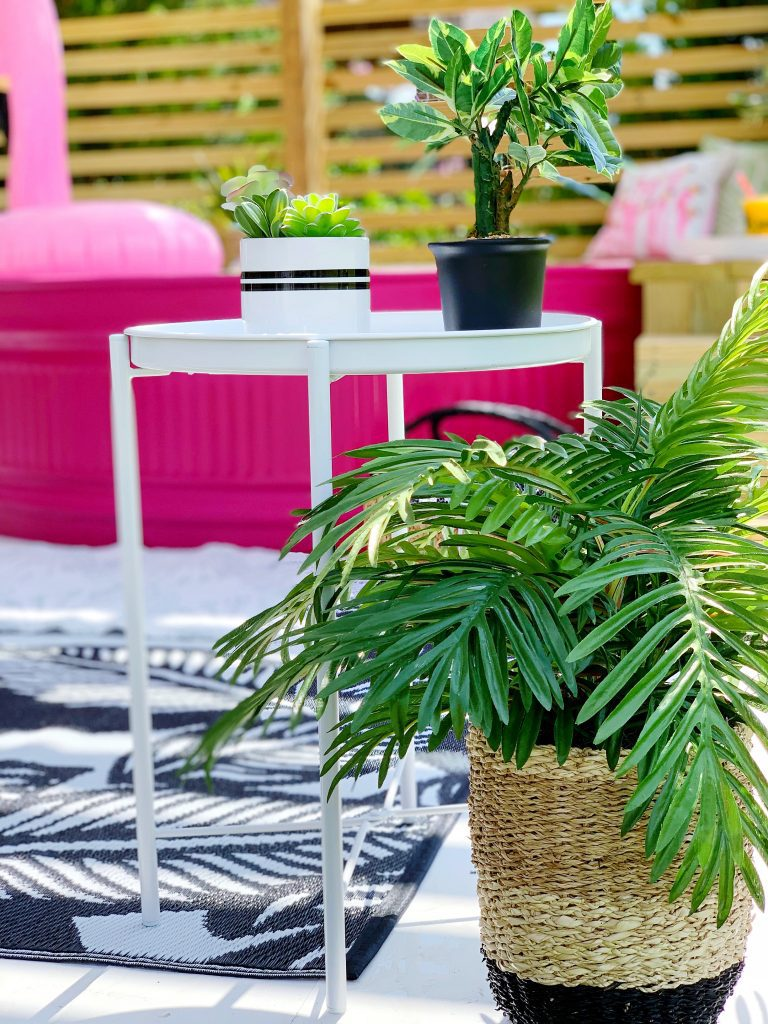 stock tank pool that is painted pink on a DIY deck with tropical rug and tropical plants