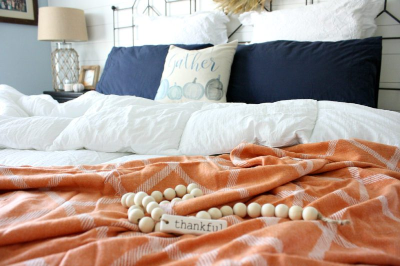 fall bedroom with thankful beads rust orange throw blanket and blue pumpkin pillow