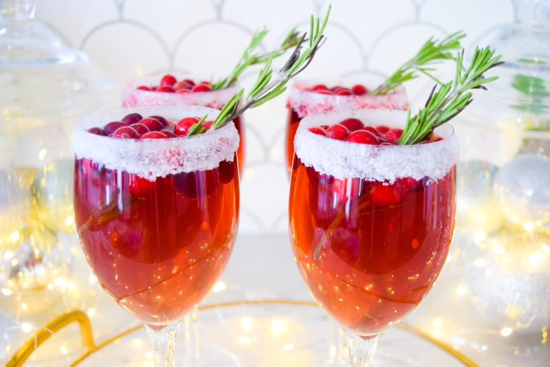 christmas cocktails with champagne, cranberry pomegranate juice, rosemary, and frozen cranberries