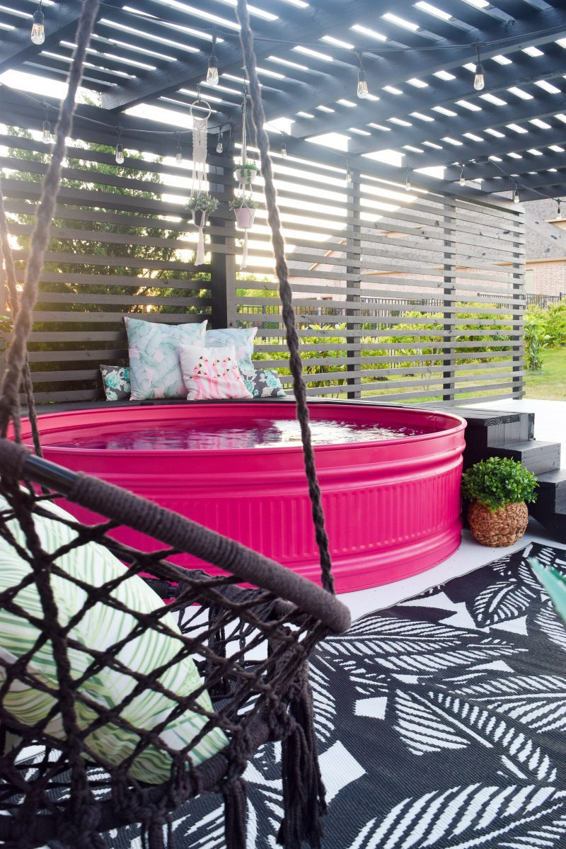 stock tank pool painted pink and hanging swing on patio deck
