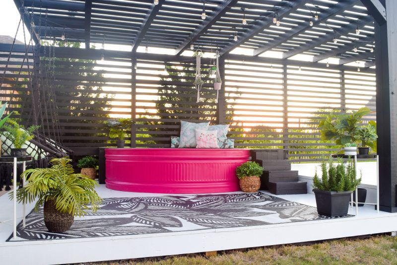 stock tank pool painted pink with black patio and white deck