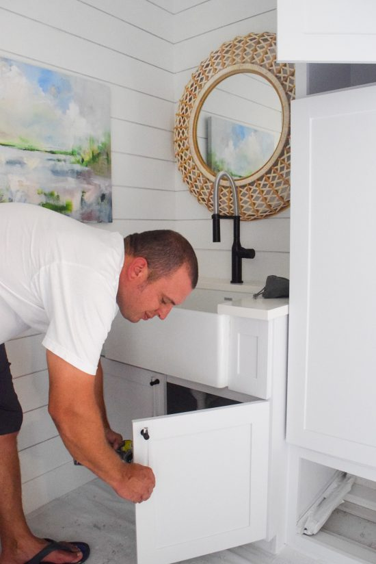 laundry room farmhouse sink with shiplap walls
