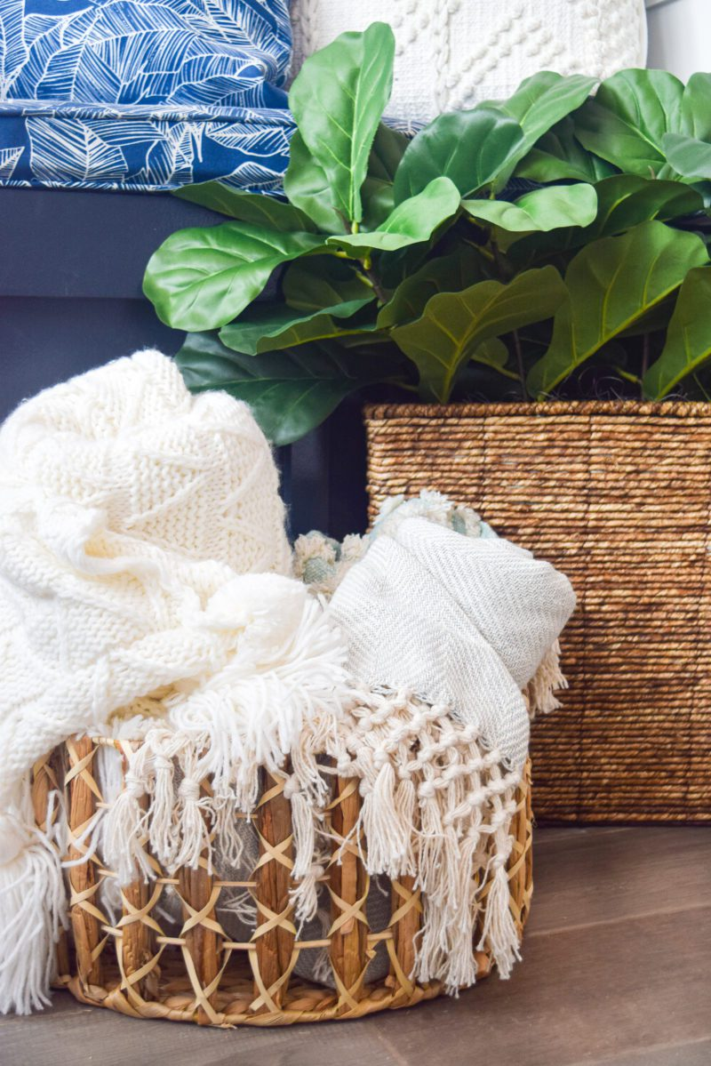 blankets in woven basket and spring plant