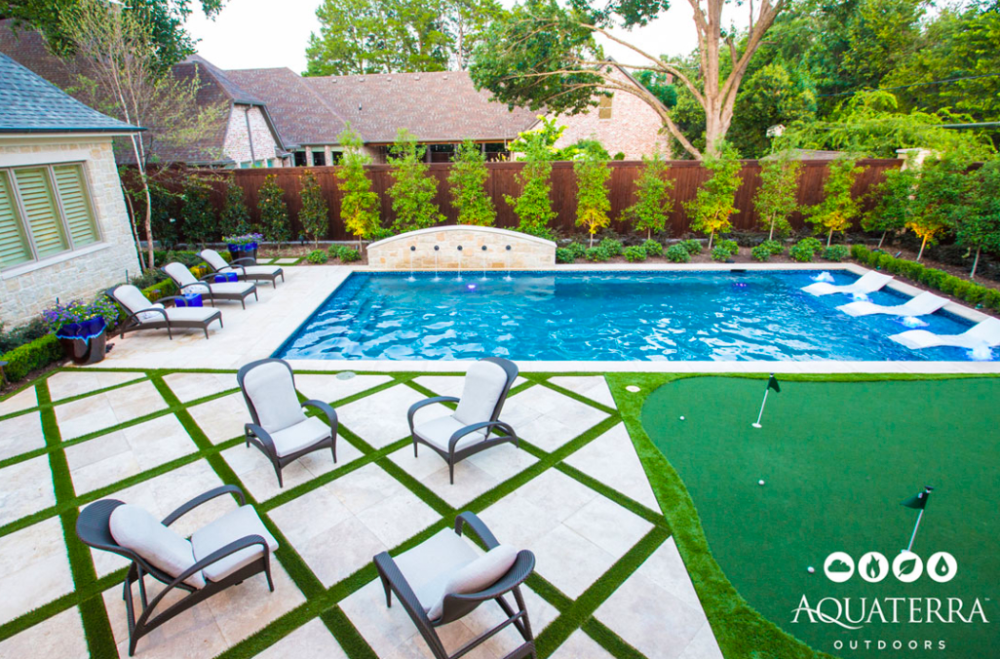 modern rectangle pool with tanning ledge pavers and turf decking and putting green in backyard