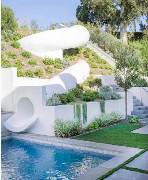 modern white pool slide on hill with stairs and landscaping